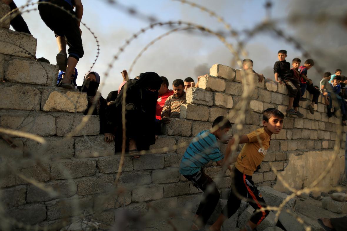 Uprchlíci přelézají zeď, aby se dostali k humanitární pomoci v uprchlickém centru na jih od Mosulu