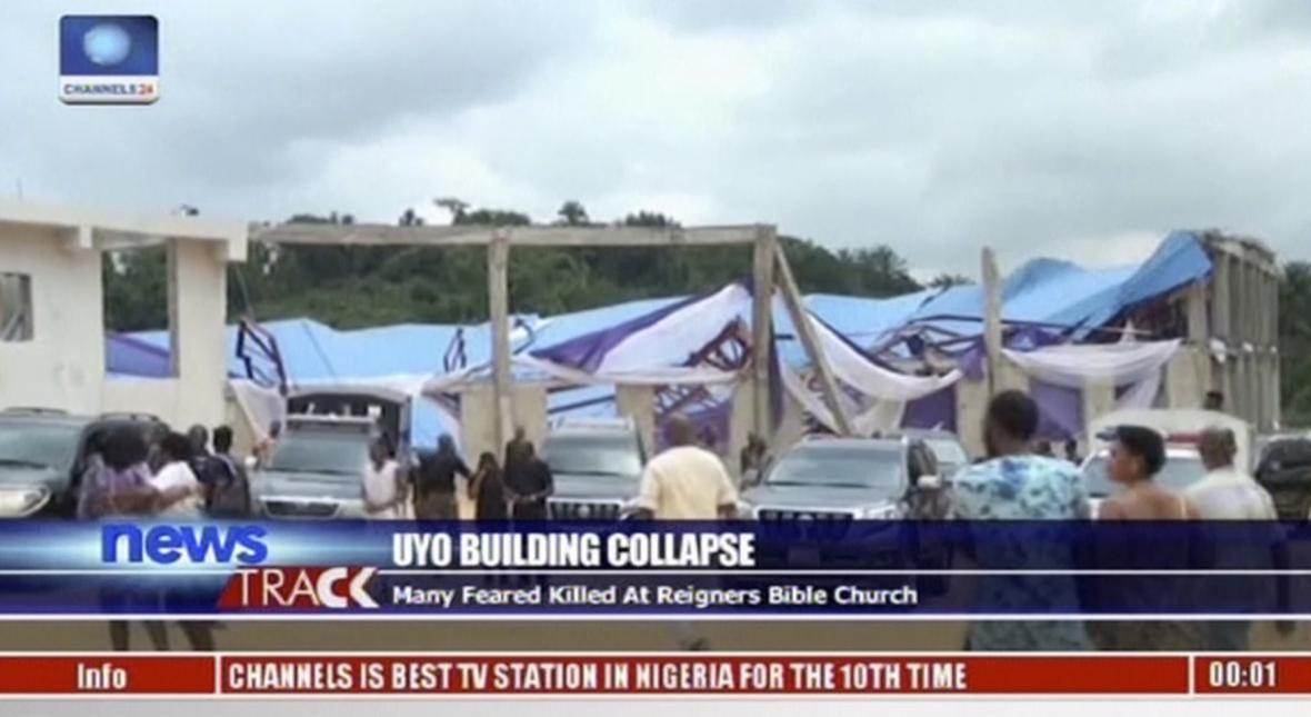 Snímek z videa zachycuje lidi stojící před zřícenou střechou kostela.