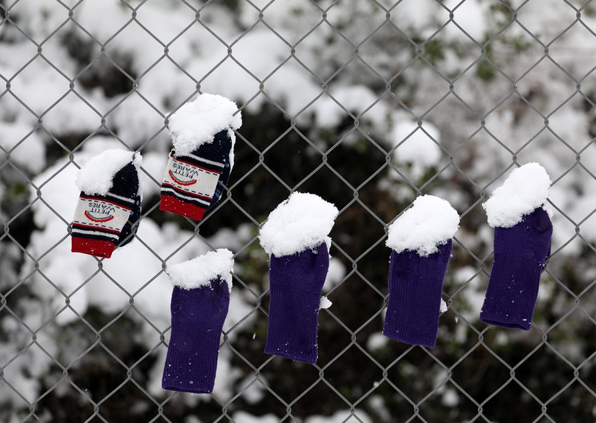 Dětské rukavice a ponožky na plotě uprchlického tábora poblíž Atén