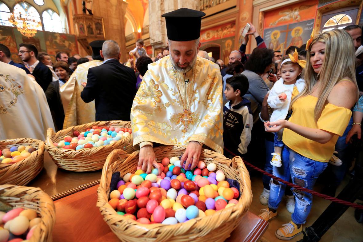 Řeckokatolický kněz v Libanonu rozděluje malovaná vejce po mši v kostele sv. Jiří v Bejrútu.
