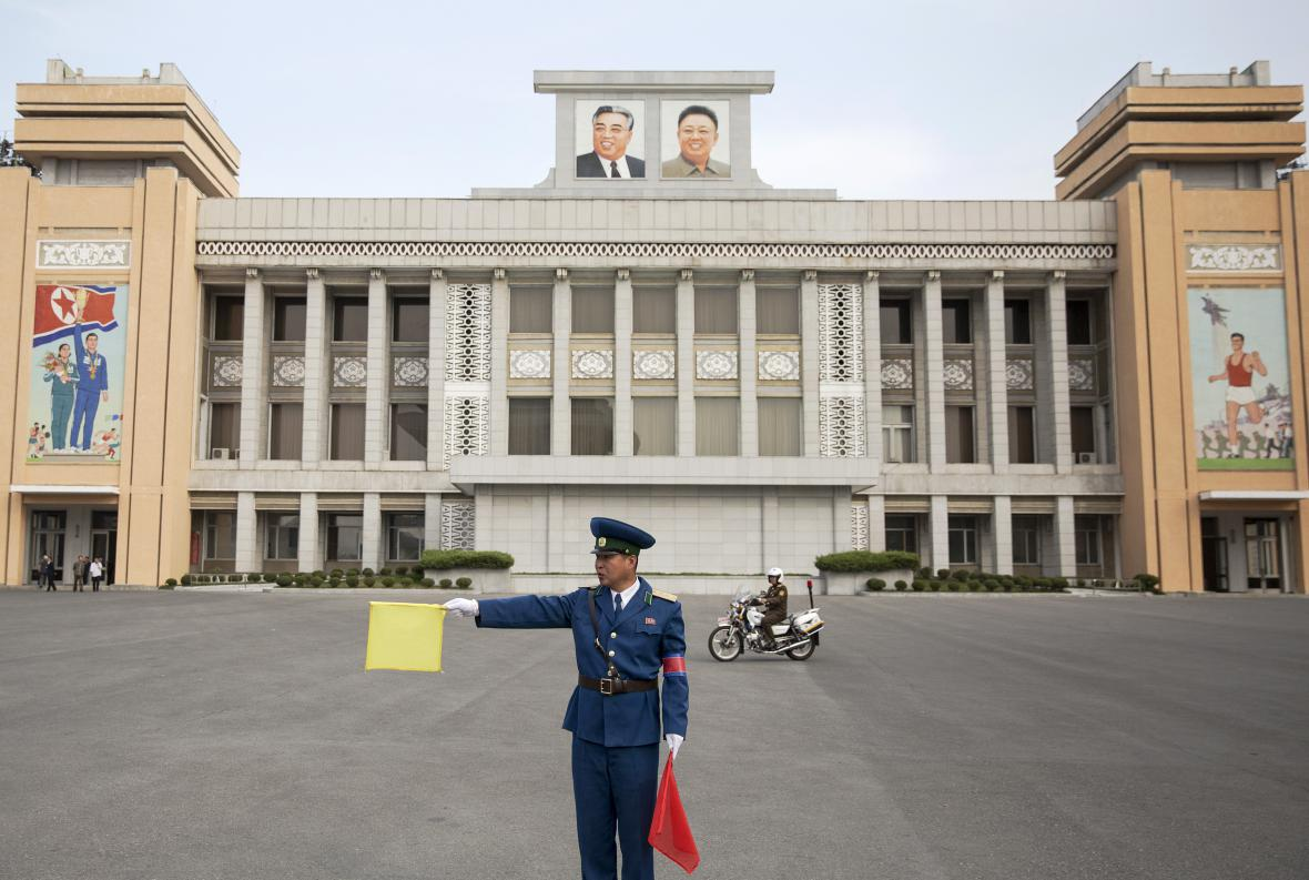 Policista řídí dopravu před jedním ze severokorejských stadionů