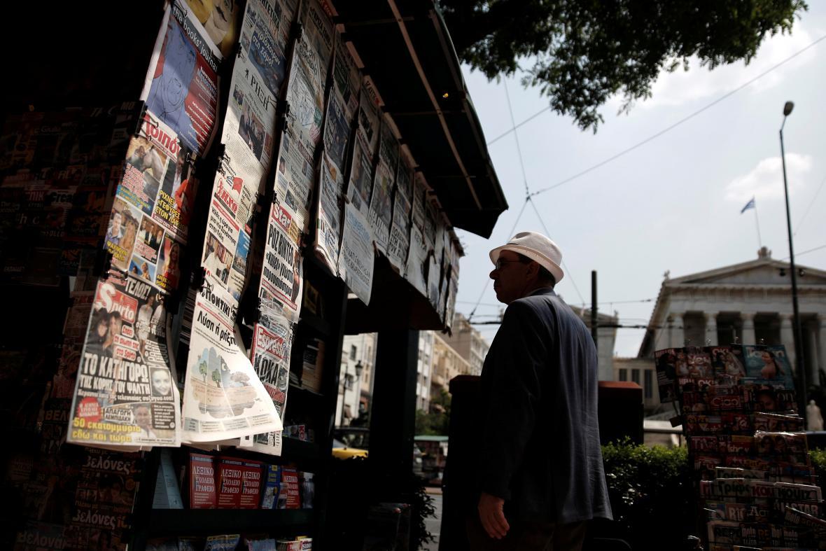 Muž v Athénách čte novinové titulky