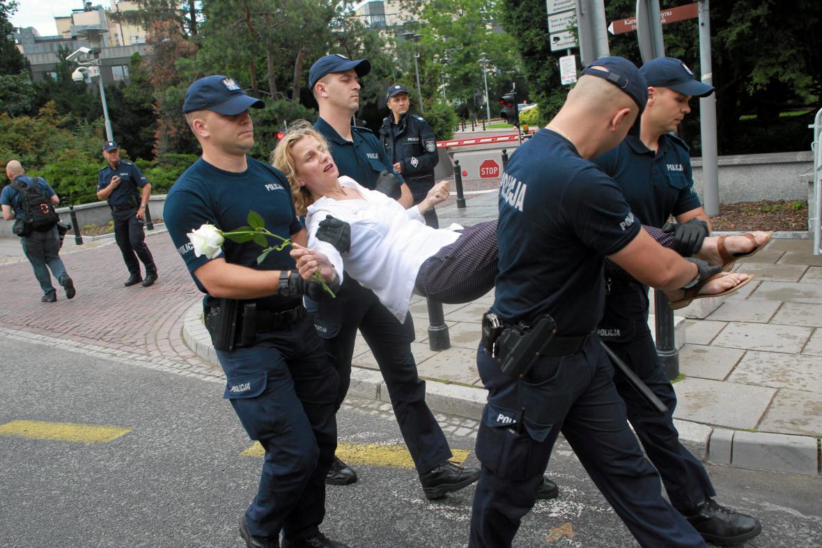 Demonstrantku odnáší v Poznani policisté během protestů proti justičním zákonům