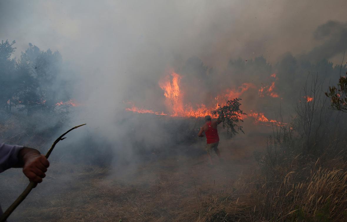 Vyhořelé pozůstatky aut následkem lesních požárů na parkovišti u kempu Bormes-les-Mimosas v regionu Var poblíž francouzské Riviéry. Tisíce lidí z kempu a místní obyvatelé byli evakuováni.