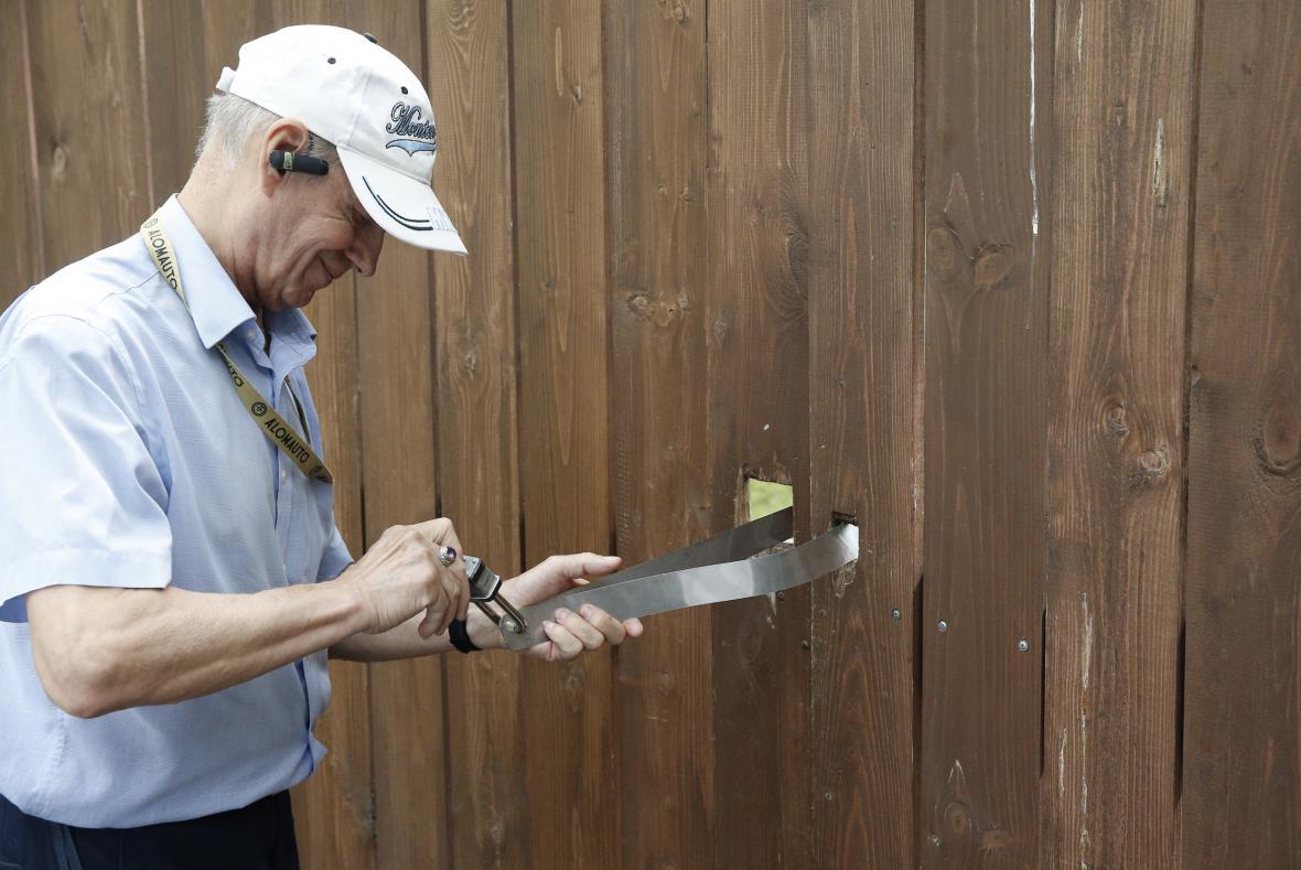 Pracovník americké ambasády zamyká bránu v areálu Serebrjanyj bor
