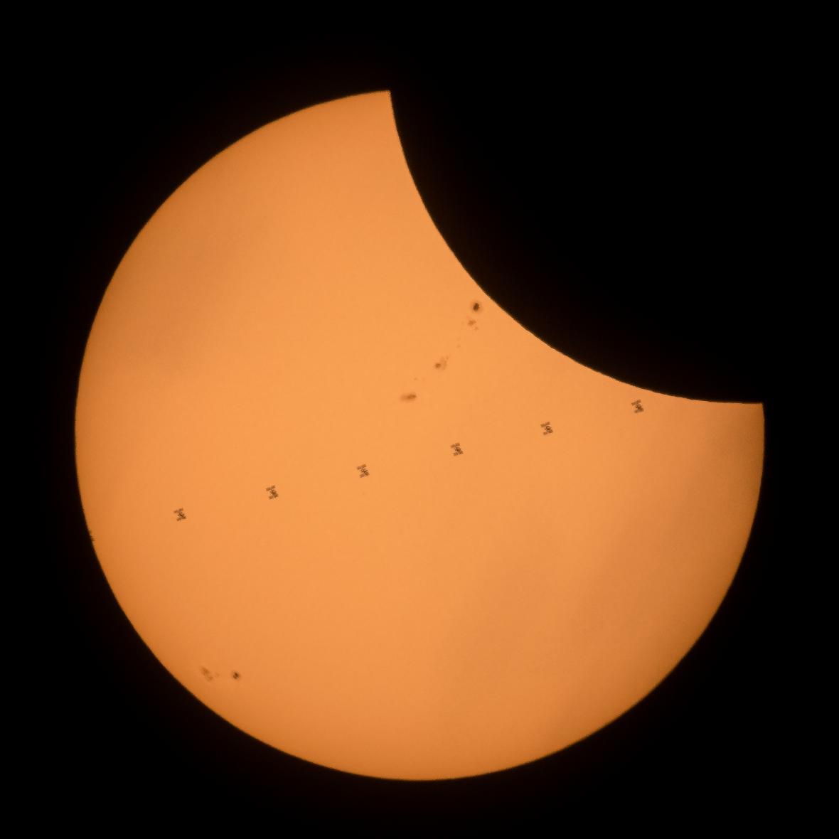 Stanice ISS před kotoučem Slunce. Kompozitní snímek