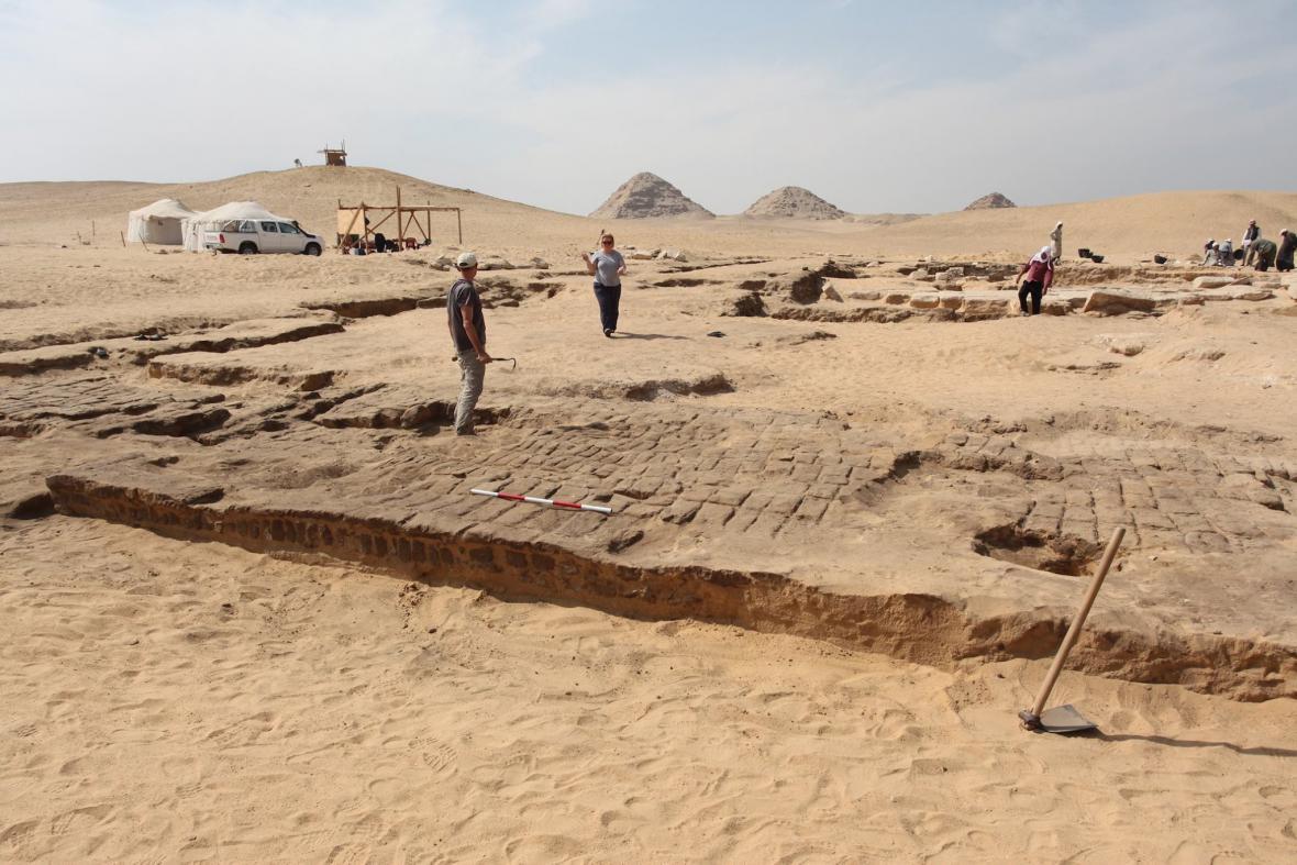 Pohled na vstupní pylon chrámu s abúsírskými pyramidami na obzoru,