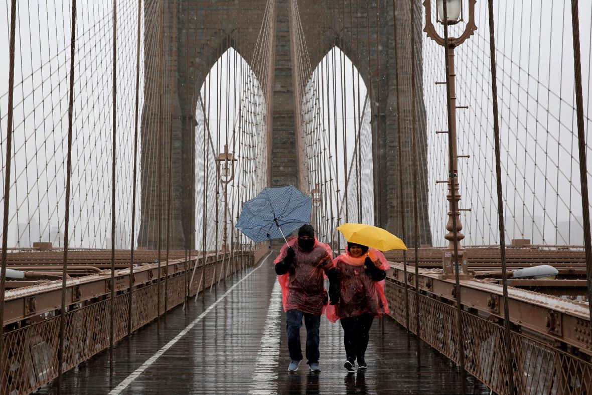 Lidé procházejí v silném větru po Brooklynském mostu
