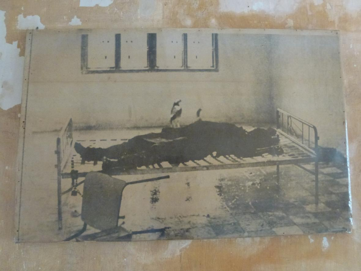 Snímek fotografie k smrti umučeného vězně, jak byl nalezen po osvobození věznice
