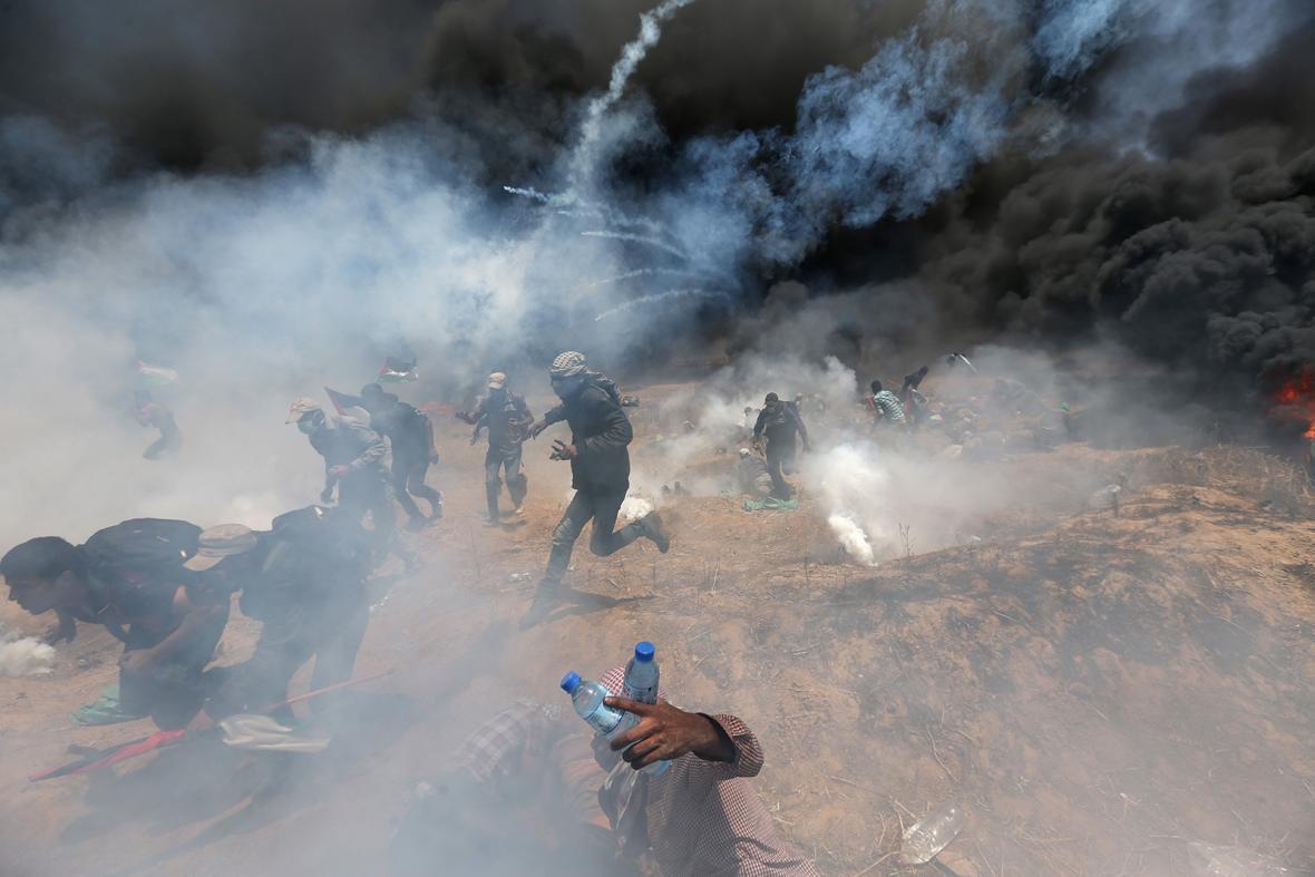 Chlapec s palestinskou vlajkou zahalen v dým z hořících pneumatik na barikádách během protestů nedaleko města Gaza