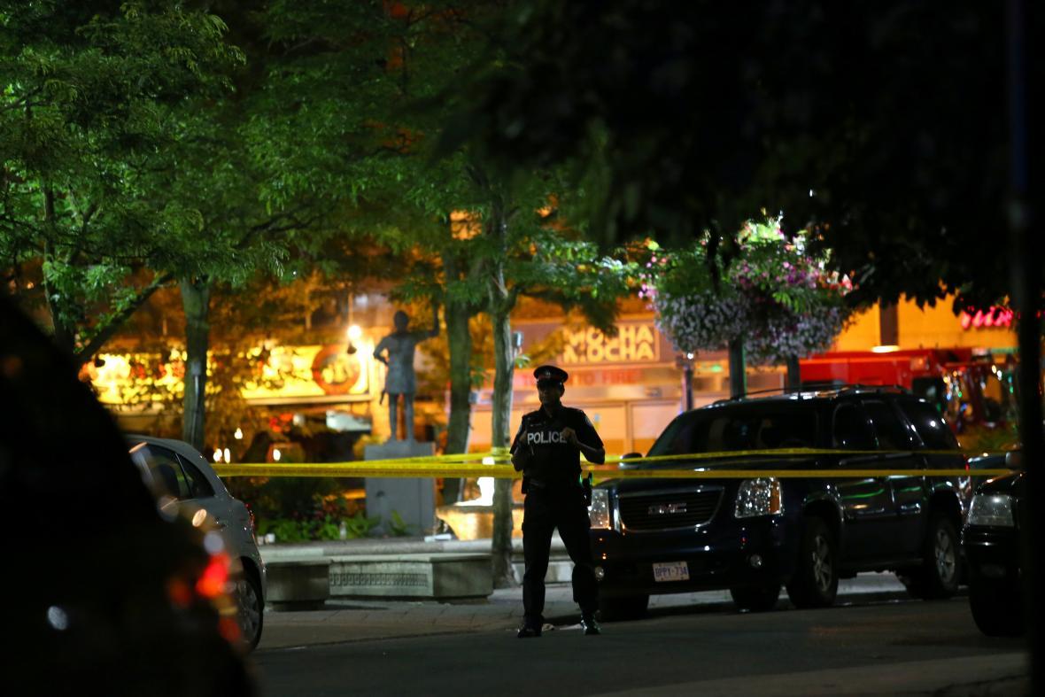 Policista střeží místo hromadné střelby v Torontu.