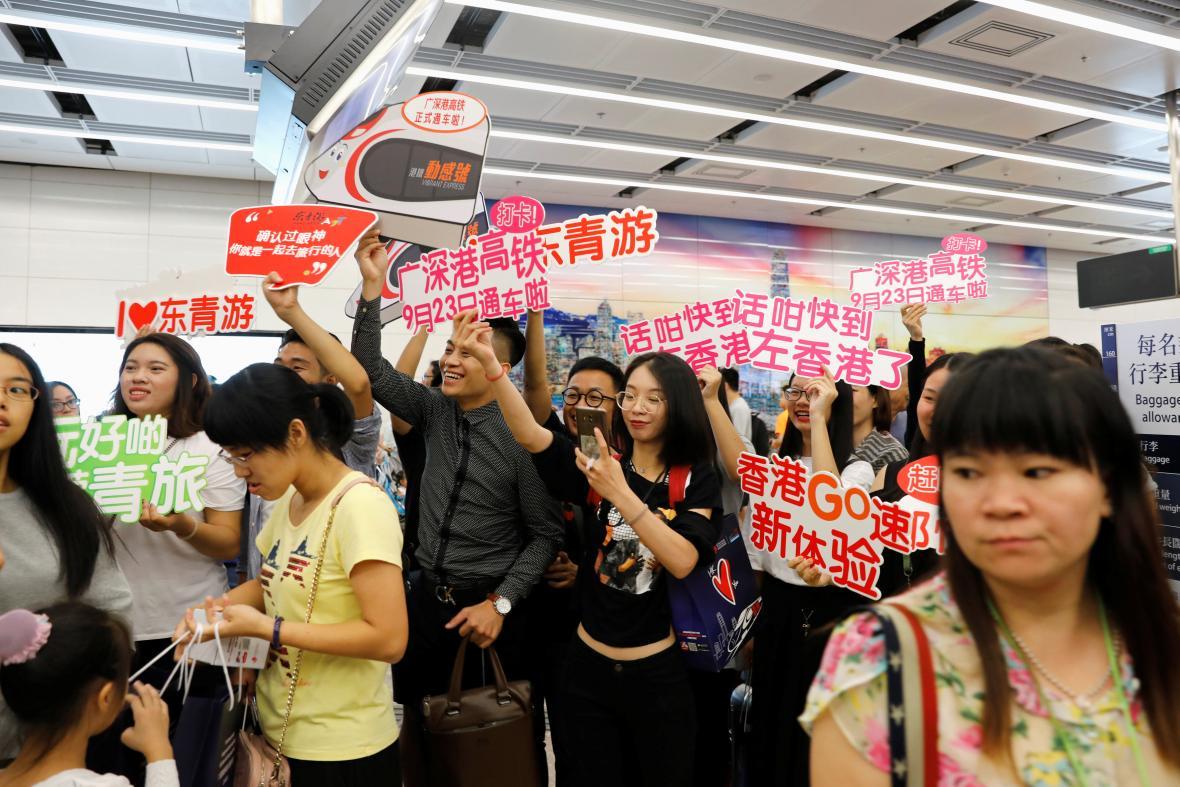 Průvodci vítají první cestující, kteří dorazili do Hongkongu z Číny rychlovlakem
