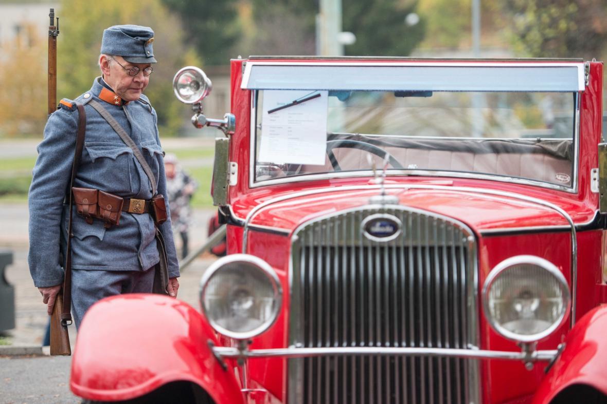 Muž v dobové vojenské uniformě si prohlíží historický automobil při oslavách ukončení války a výročí 100 let ČSR v Jablonci nad Nisou