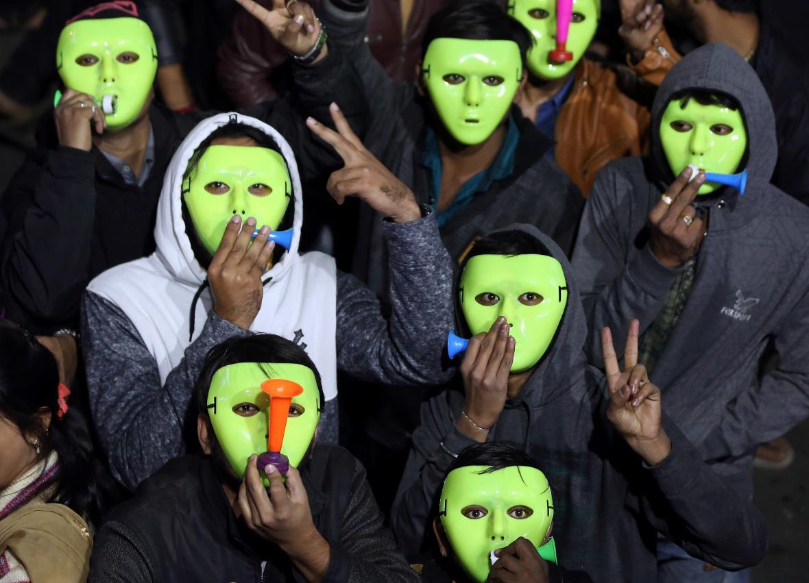 Lidé v maskách v indickém Ahmadábádu odpočítávají půlnoc