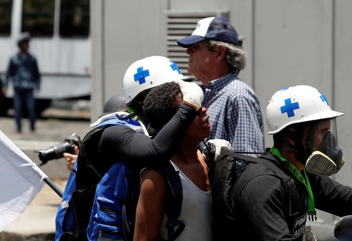 Záchranáři pomáhají zraněným při střetech mezi opozičními demonstranty a bezpečnostními silami v blízkosti letecké základny Generalisimo Francisco de Miranda