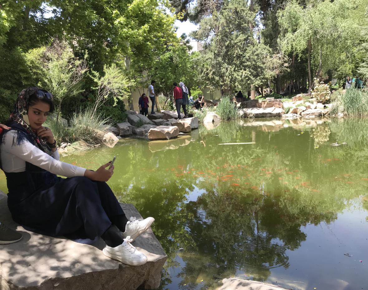 Mladá Íránka si dělá selfie v zahradě Eram v Šírázu