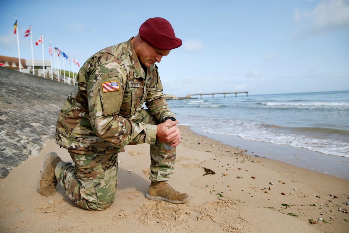 Americký voják na pláži Omaha drží v ruce písek, na kterém prolívali krev jeho předchůdci