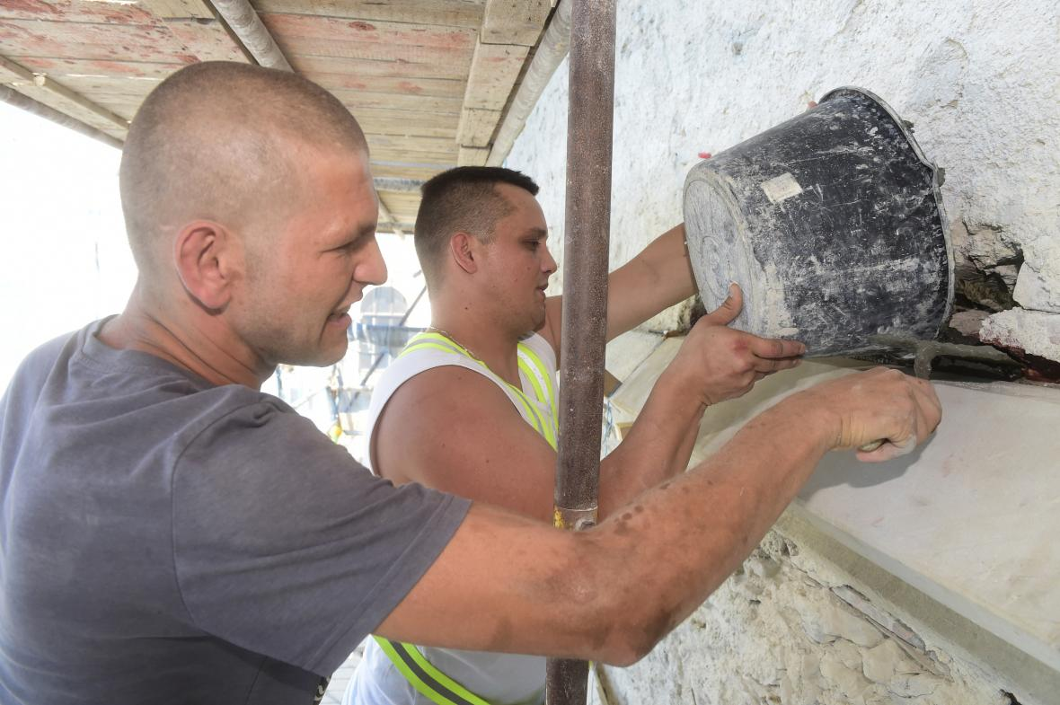 Kameníci lepí nové části římsy z maletínského pískovce.