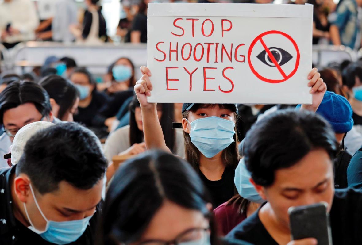 Demonstranti si na protest proti zranění medičky gumovým projektilem zakrývají oko páskou s falešnou krví