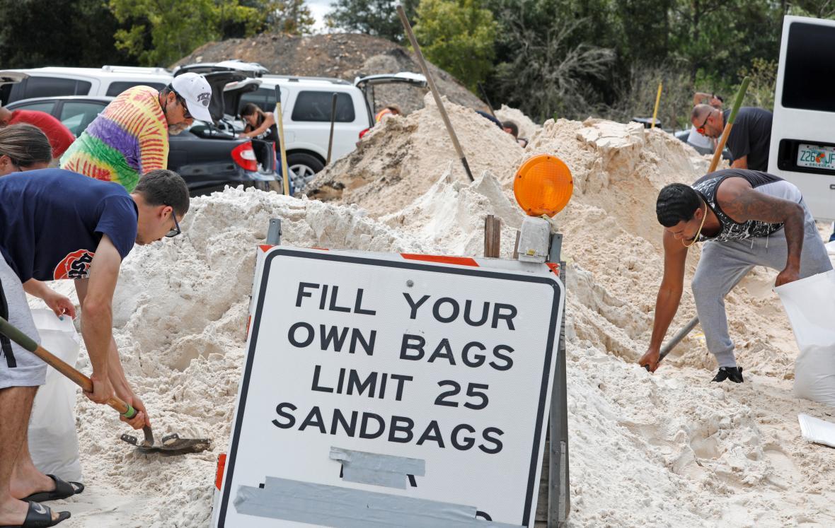 Lidé nabírají písek do pytlů k ochraně domů před záplavou