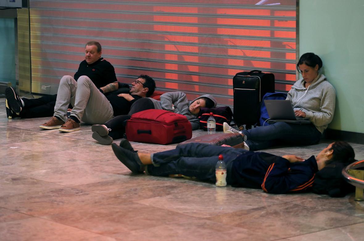Uvízlí cestující čekají na podlaze příletové haly na letišti v Alicante