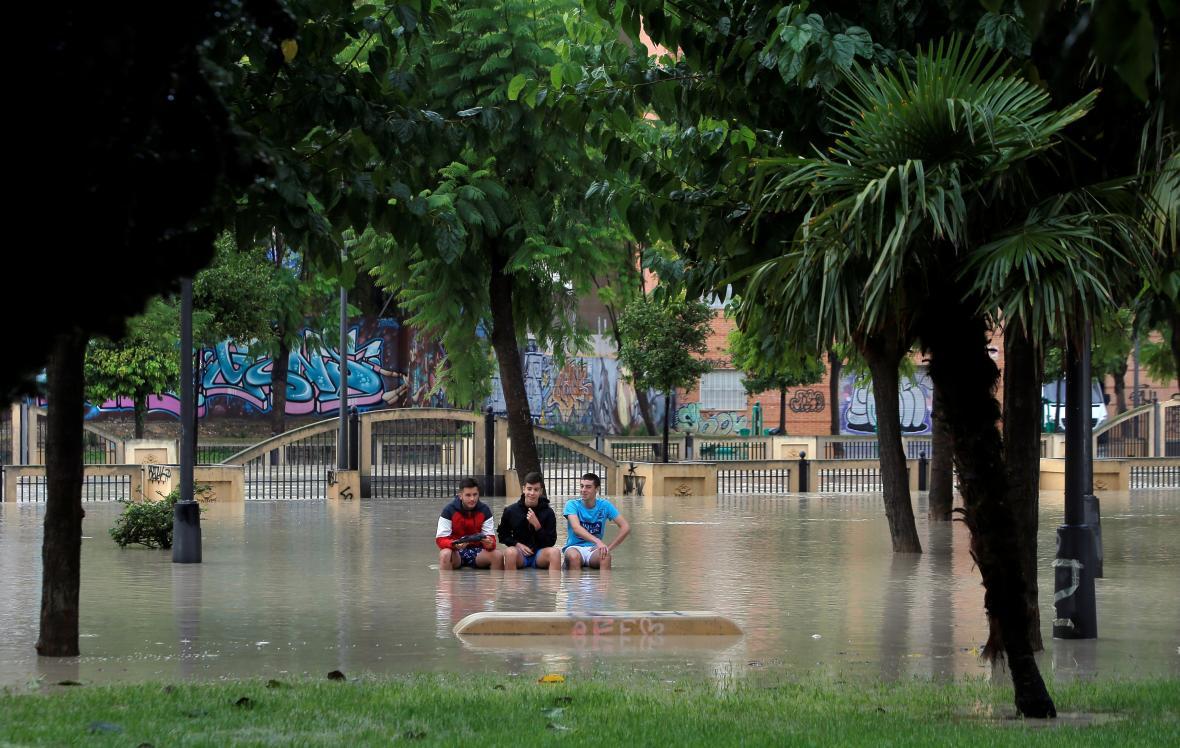 Mladíci sledují v parku rozvodněnou řeku