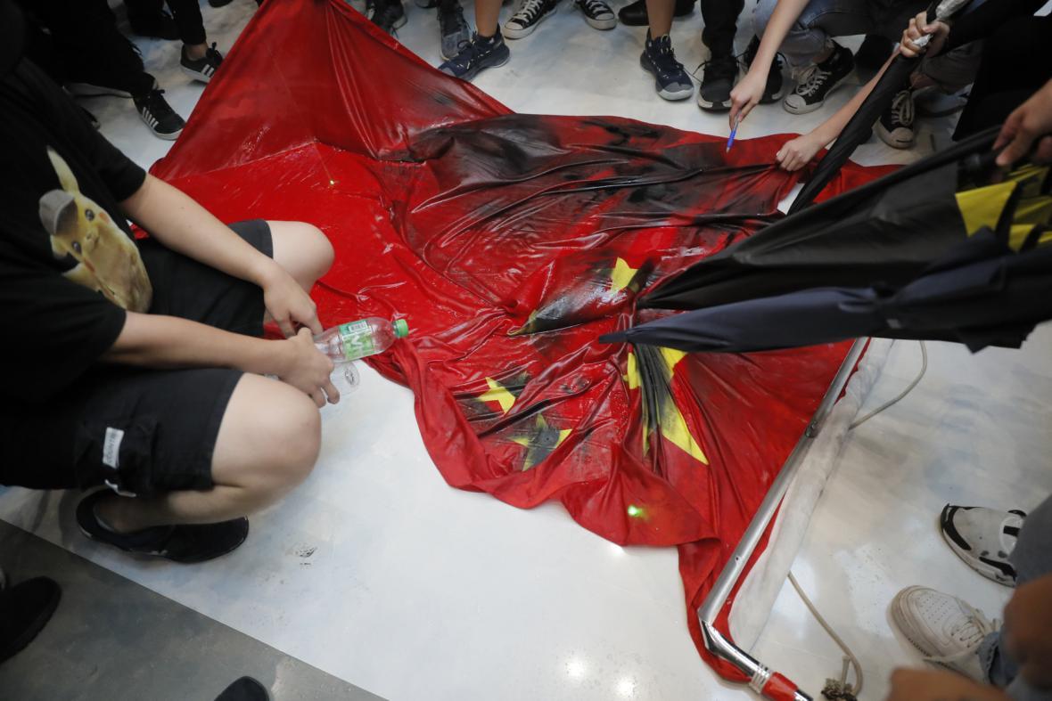 Skupina demonstrantů uprostřed nákupního střediska šlapala po čínské vlajce, kterou poté roztrhanou hodila do blízké řeky.