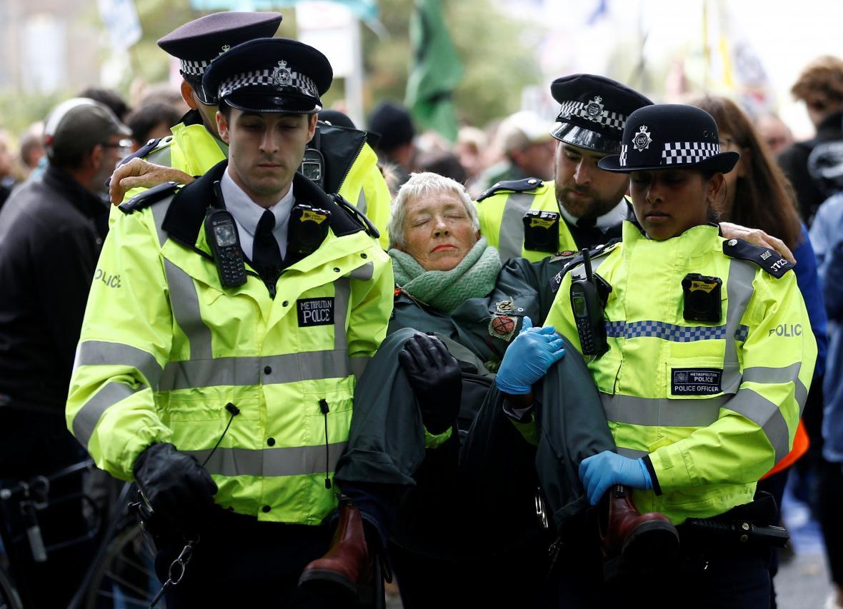 Policisté odnáší jednu z protestujících z hnutí Vzpoura proti vyhynutí