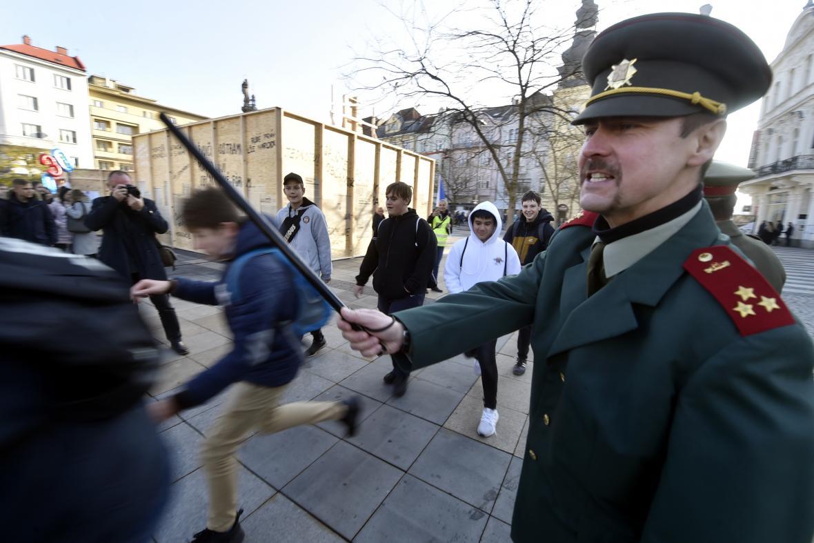 Herci v dobových uniformách Sboru národní bezpečnosti rozhánějí lidský řetěz podobný tomu, který vytvořili Ostravané v listopadu 1989