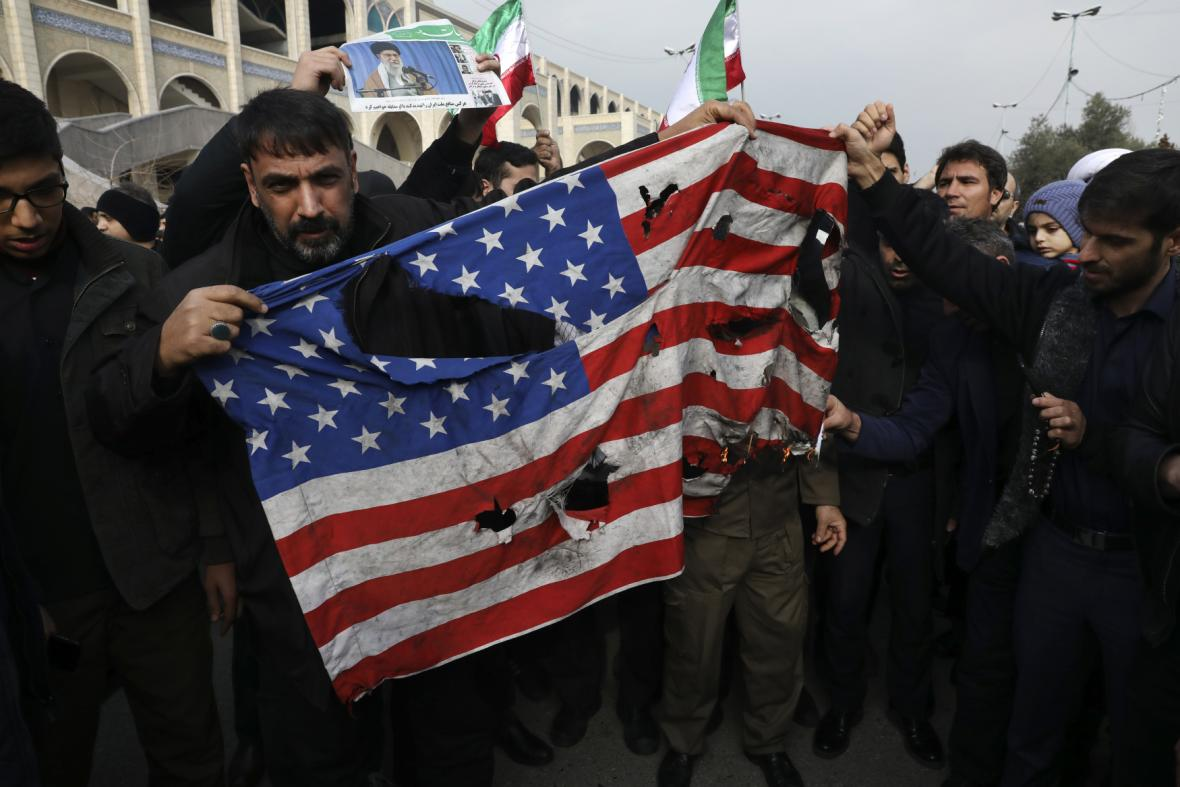 Demonstranti s roztrhanou americkou vlajkou během protestů v Teheránu