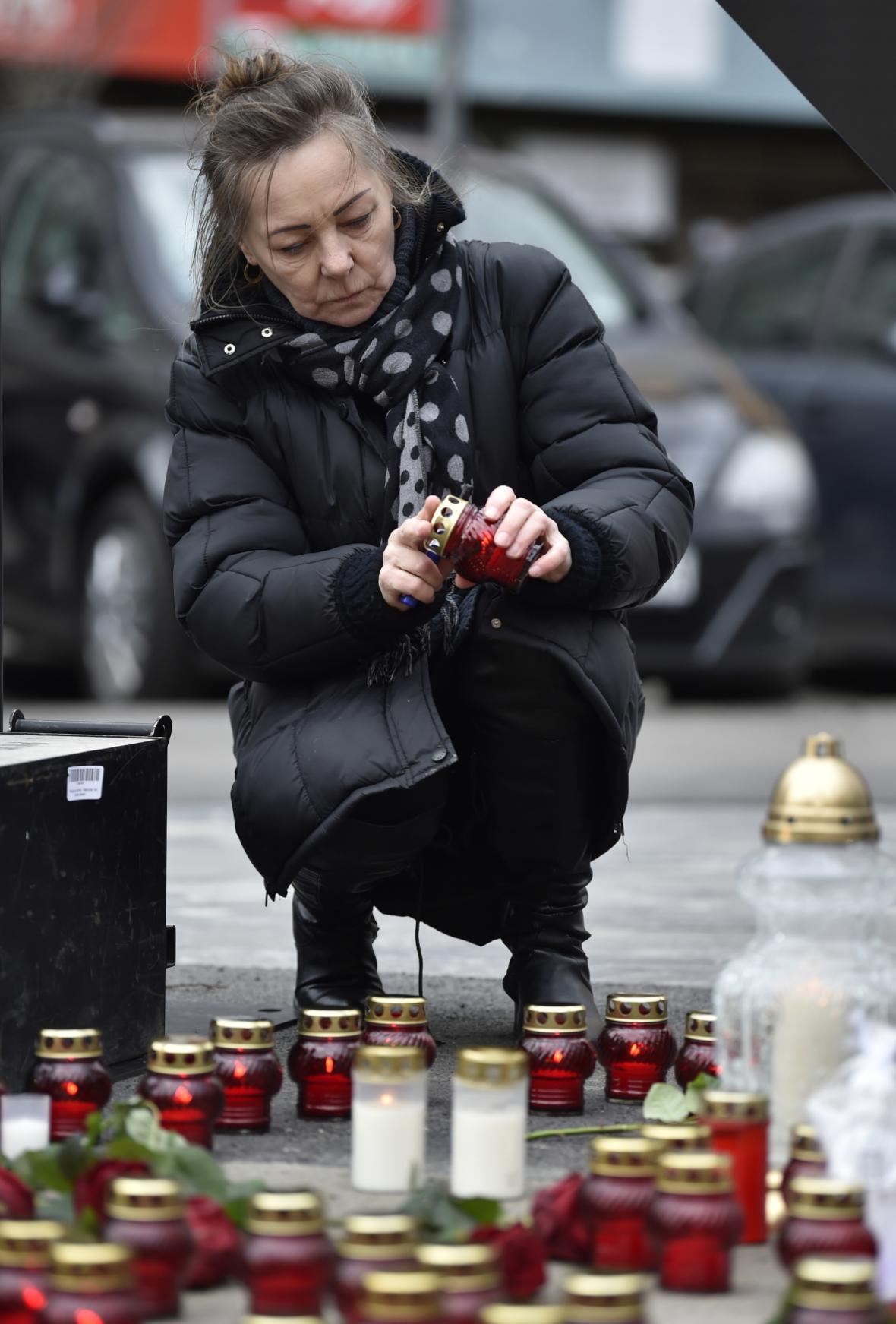 Žena zapaluje svíčku na Náměstí SNP  v Bratislavě