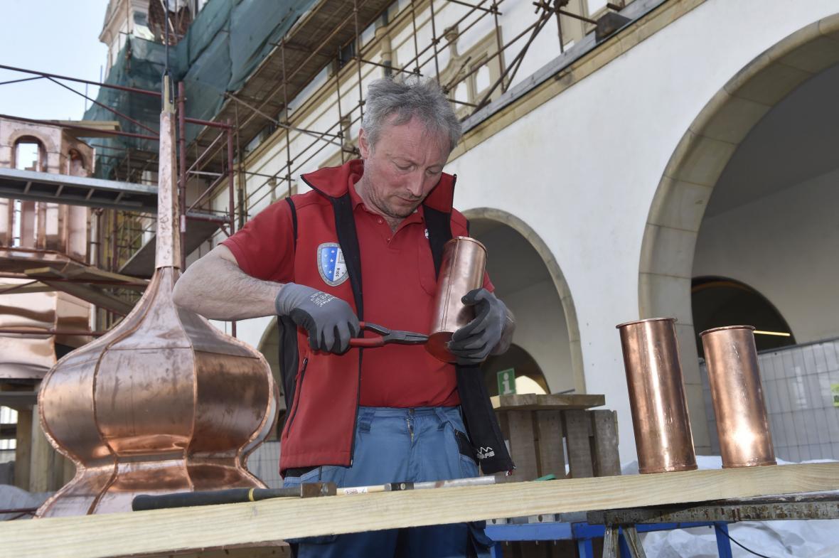 Klempíř František Žíla uzavírá nové kovové schránky s historickými či soudobými materiály, které vložil do makovice věžičky nad orlojem