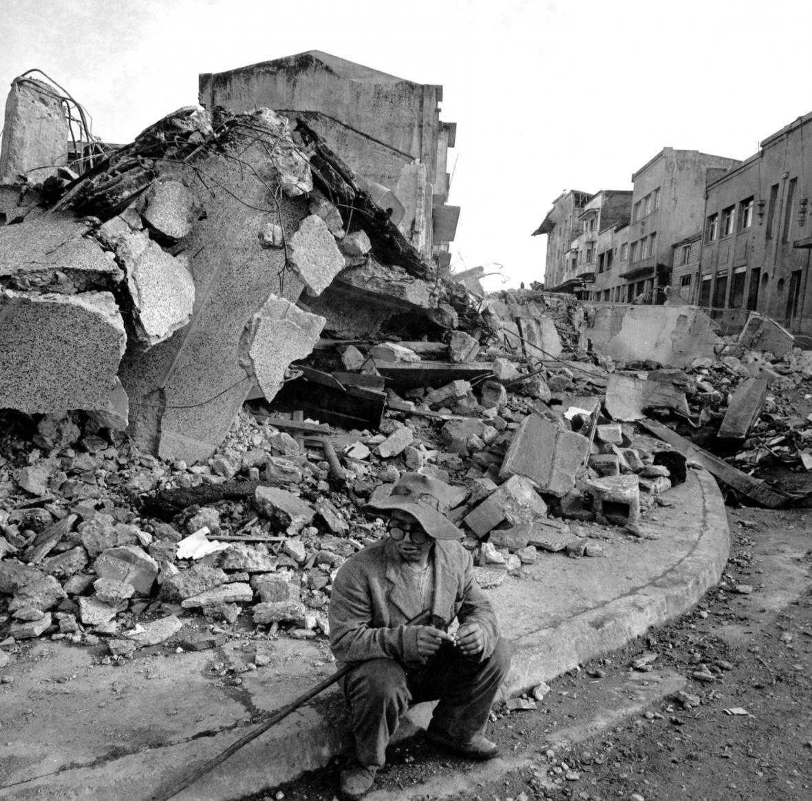 Osamělý obyvatel města Chile na jihu země sedí na obrubníku v centru města poté, co byla sekce zasažena ničivými zemětřeseními. Sutiny v pozadí byly obchodní centrum. Snímek z  30. května 1960