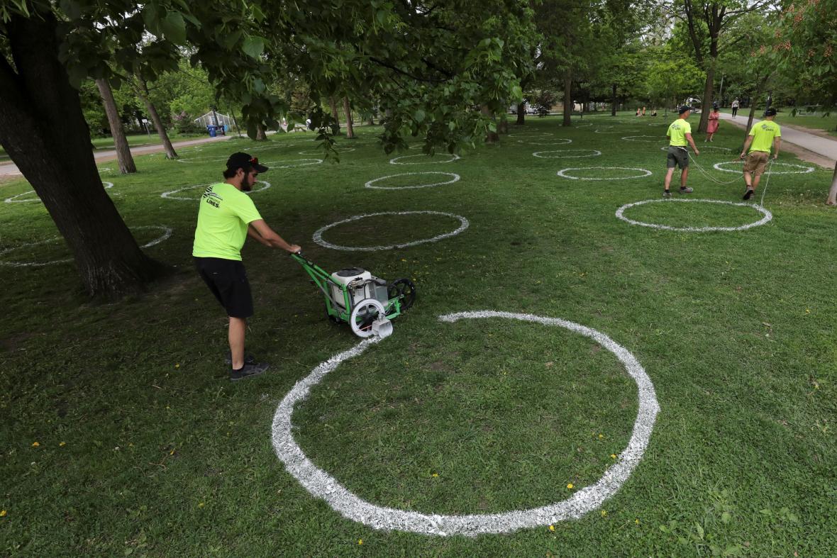 V Trinity Bellwoods parku v Torontu netřeba vzdálenost odhadovat, kruhy v trávě ukazují, kam je možné si bezpečně sednout