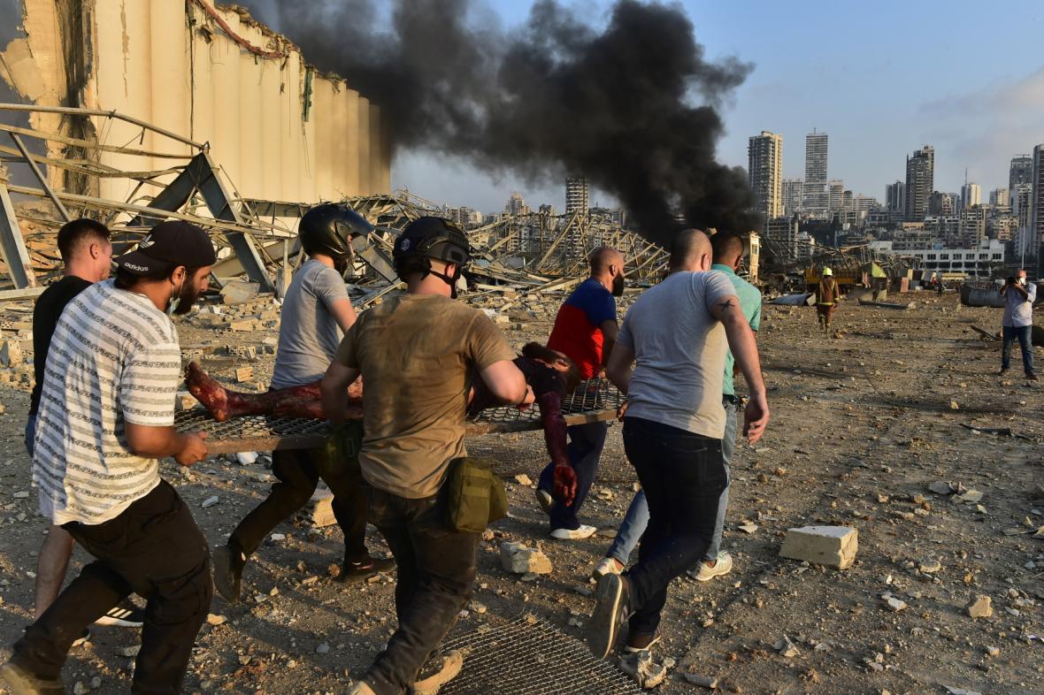 Civilisté odnášejí zraněného na provizorních nosítkách