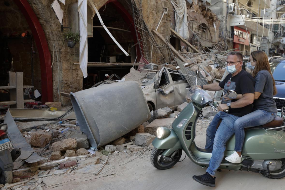 Lidé jedoucí na motorce troskami Bejrútu