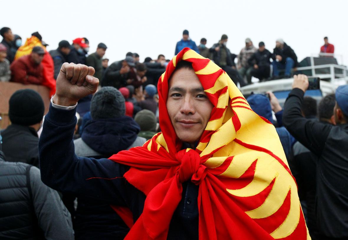 Jeden z protestujících s uvázanou kyrgyzskou vlajkou kolem krku gestikuluje během demonstrací