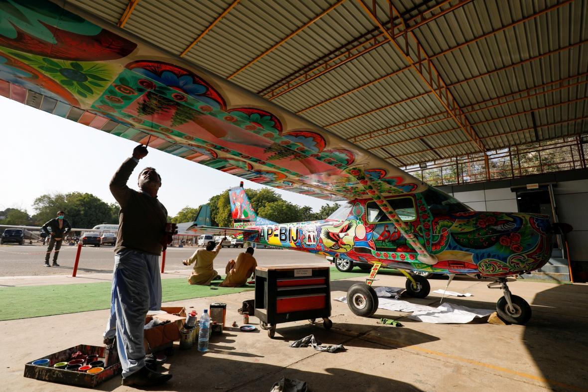 Umělečtí malíři zdobí letadlo Cesnna v jednom z hangáru na mezinárodním letišti v pakistánském Karáčí