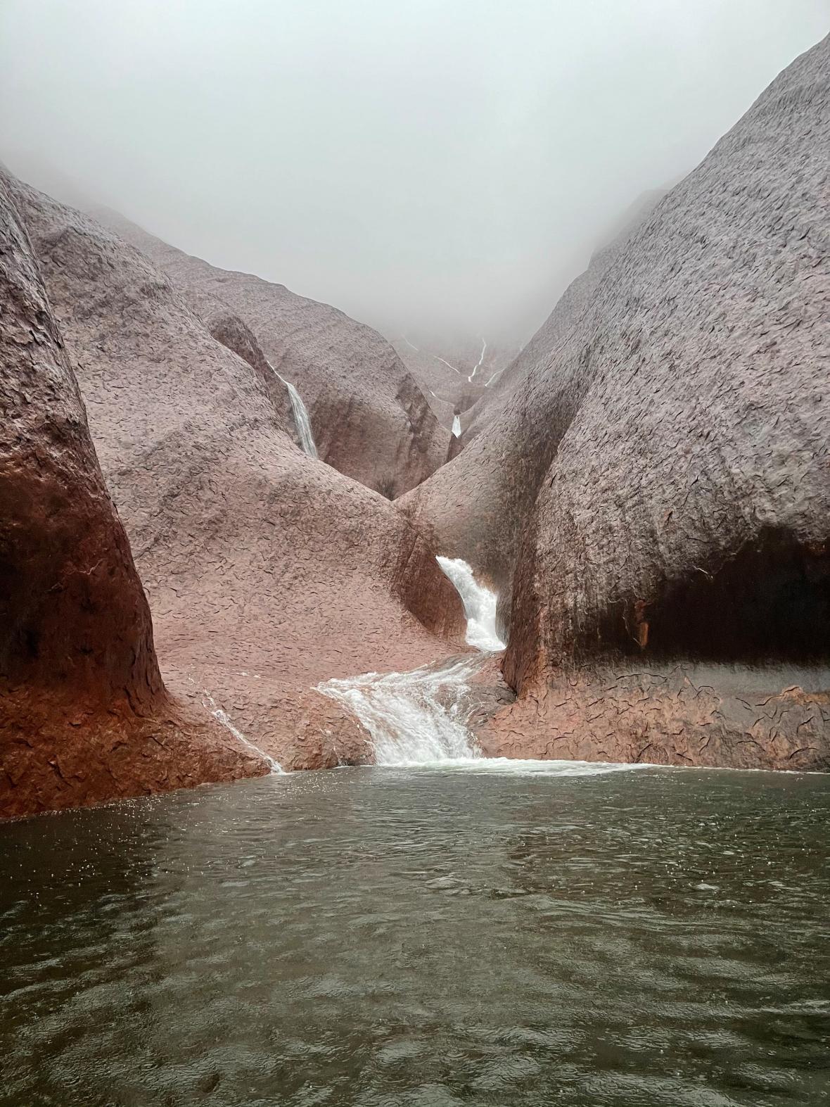 Skalními stěnami Uluru burácí voda.