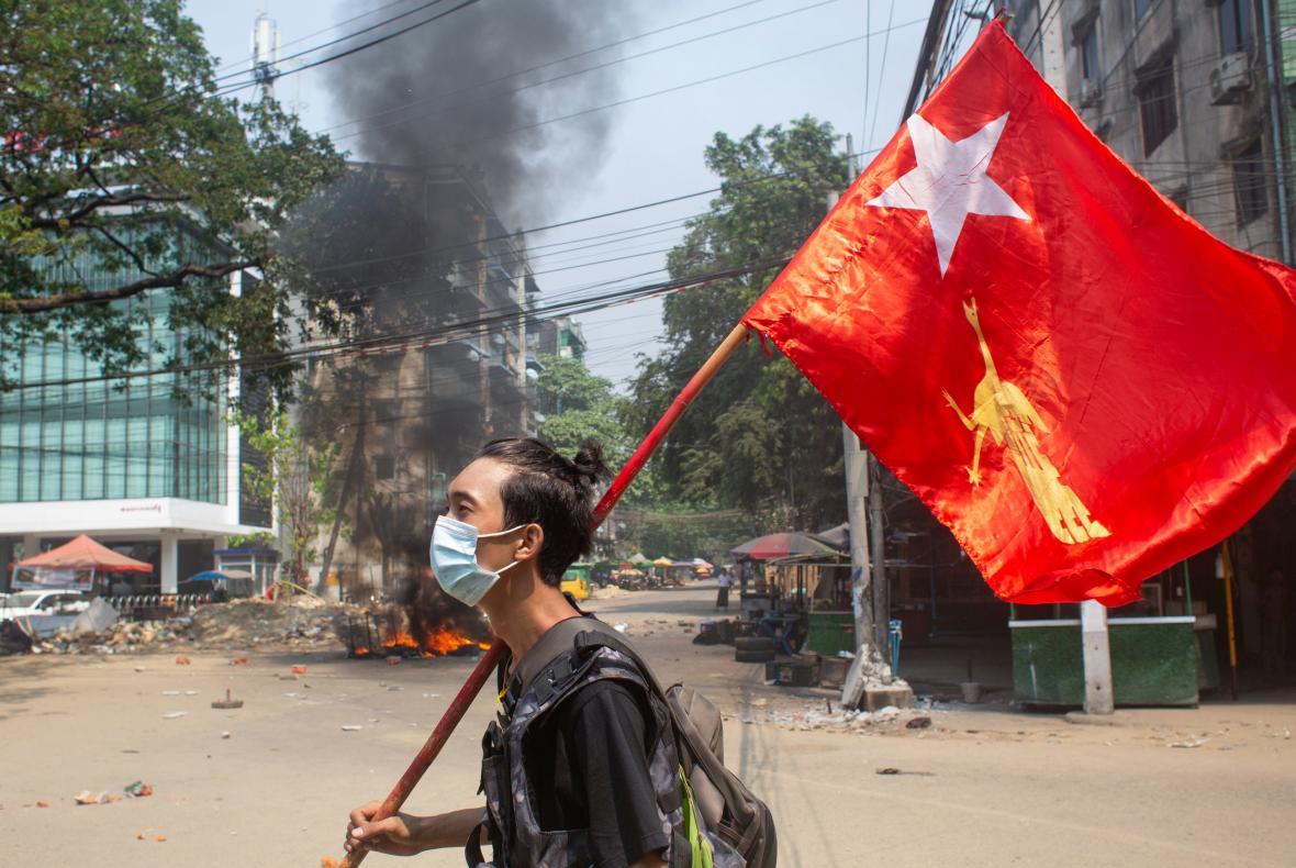 Myanmarský demonstrant drží vlajku Národní ligy pro demokracii