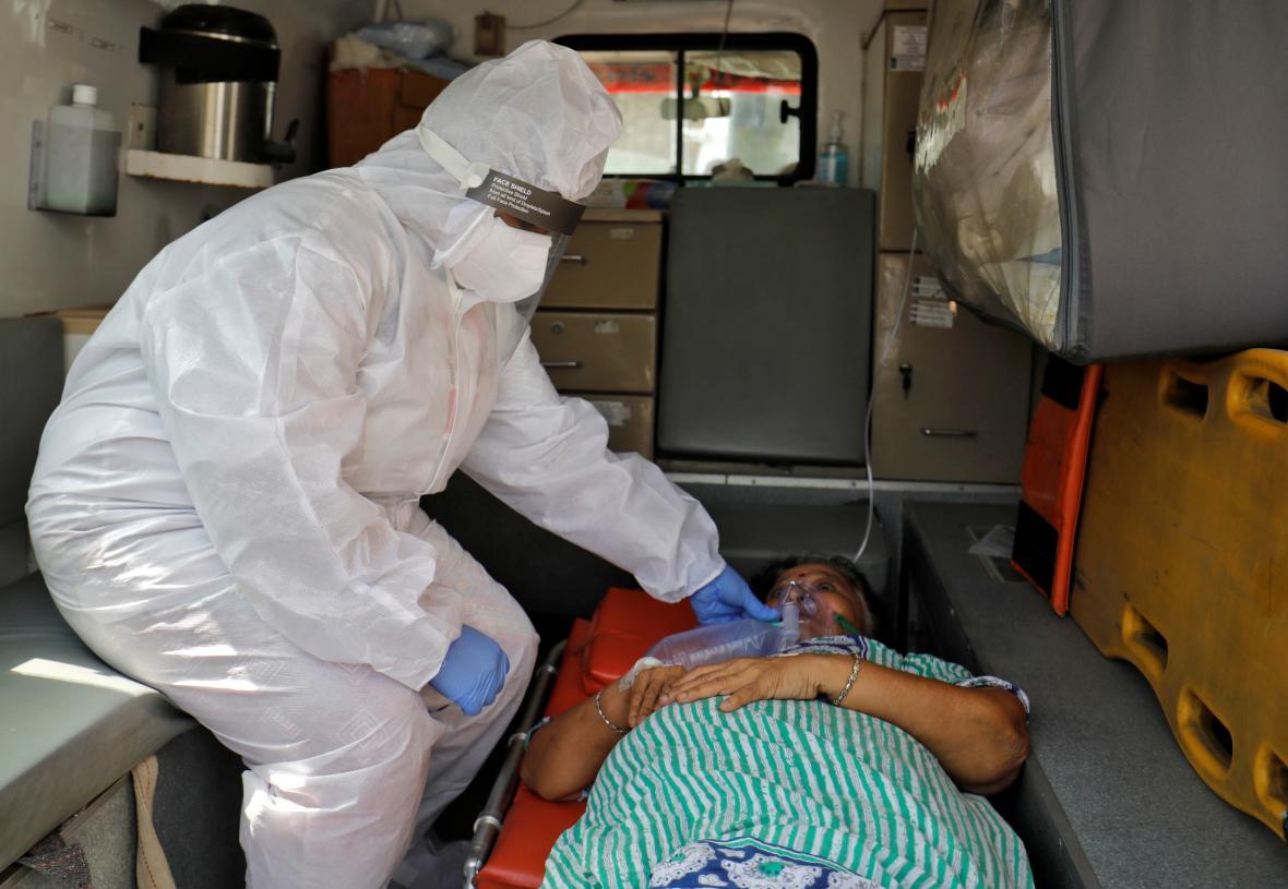 Indický zdravotník podává nemocné ženě kyslík