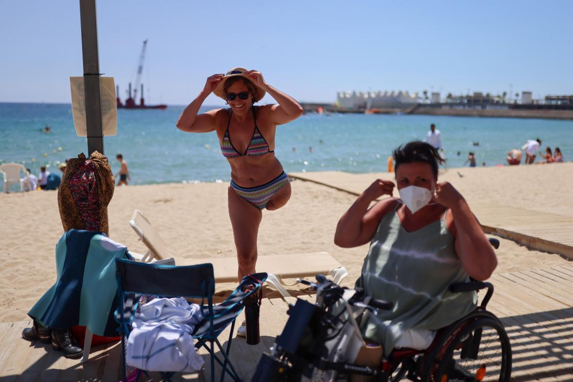 Plavčíci z pláže Nova Icaria ve Španělsku pomáhají lidem se zdravotním postižením s plaváním v moři