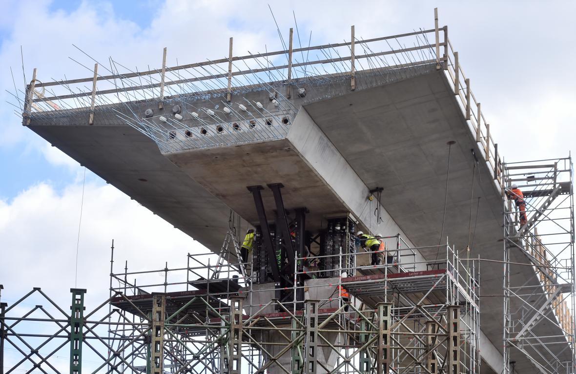 Stavbaři začali 12. října 2021 usazovat mostní konstrukci nad tratí, po níž vlaky jezdí přes Havlíčkův Brod mezi Prahou a Brnem