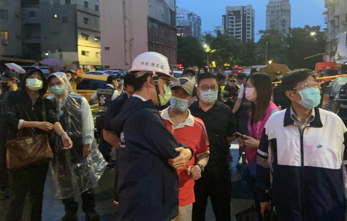 Lidé čekají před budovou zasaženou ohněm na zprávu o osudu svých příbuzných