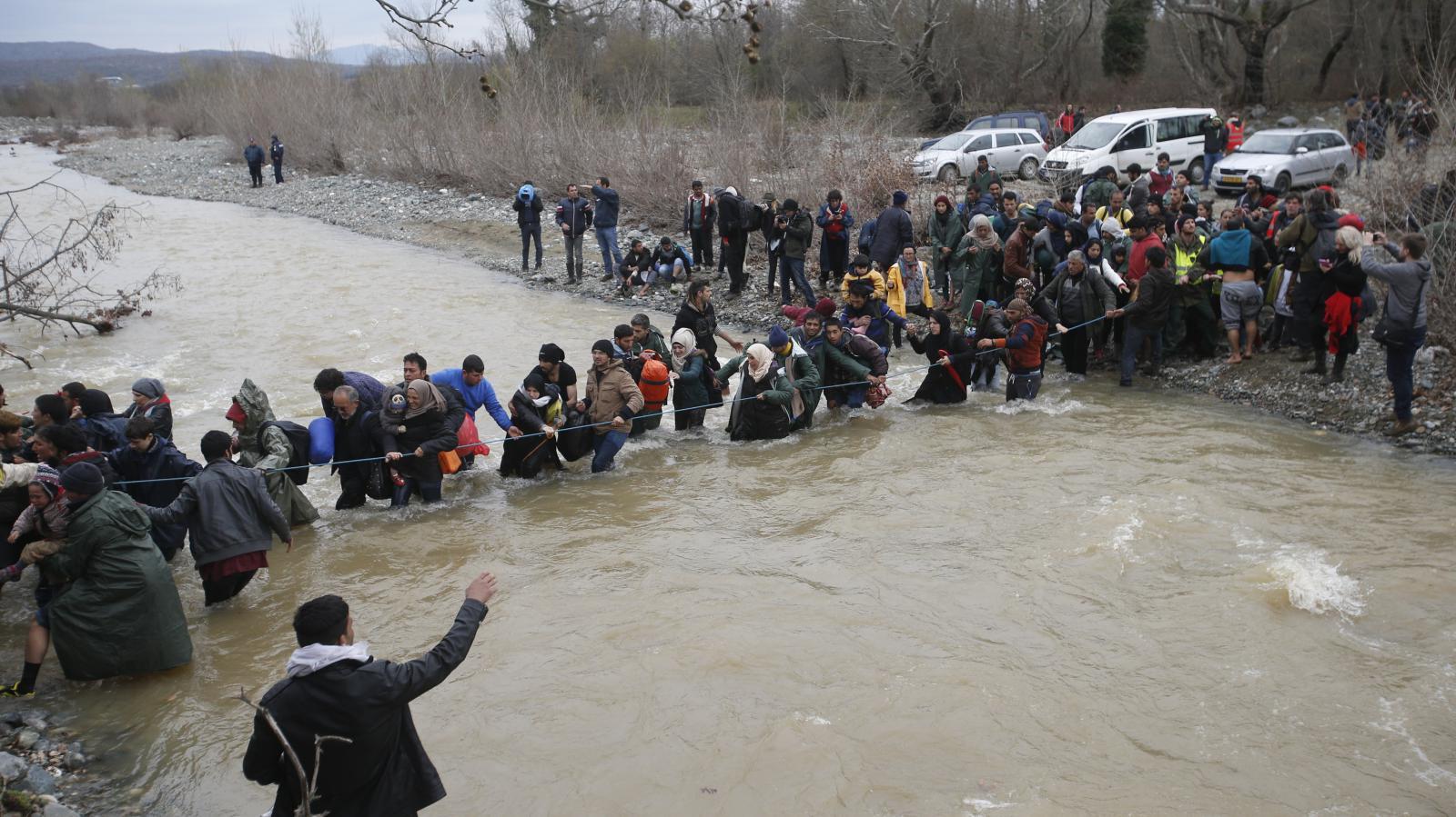 Uprchlíci a dobrovolníci vytvořili živý řetěz přes řeku u hranice Řecka a Makedonie