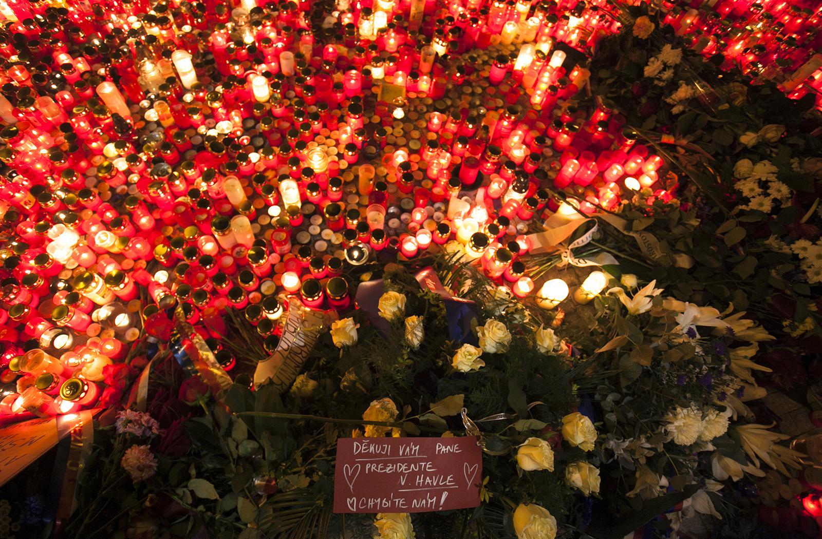 Zapálené svíčky a květiny na Národní třídě