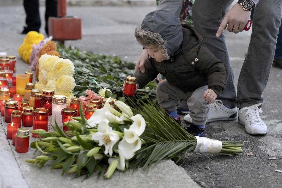Příbuzní obětí přicházejí položit ke klubu květiny