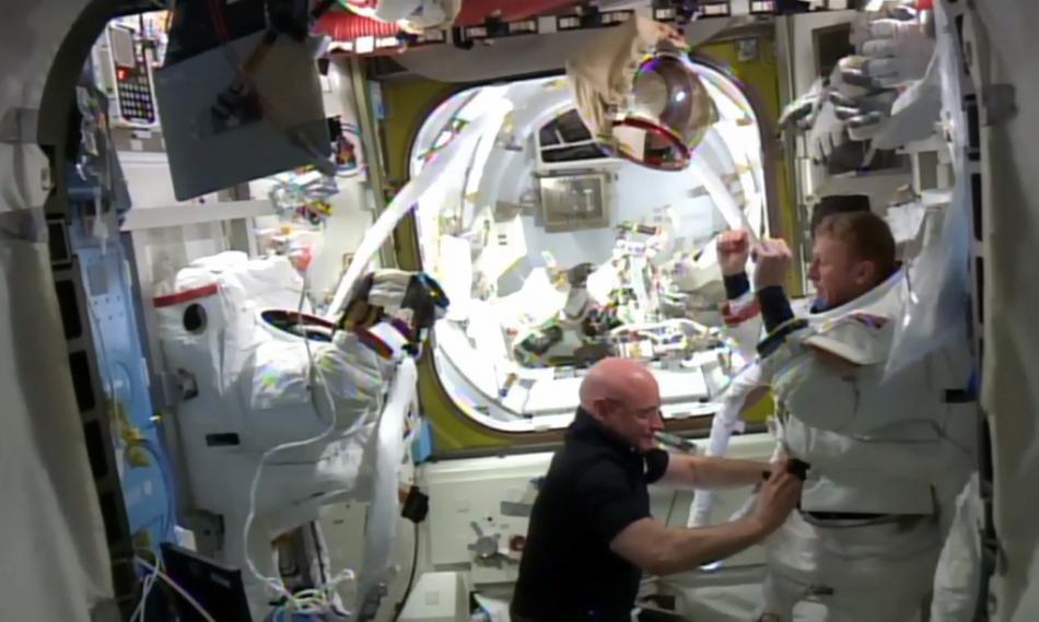 Velitel ISS Scott Kelly pomáhá Timu Peakovi ze skafandu