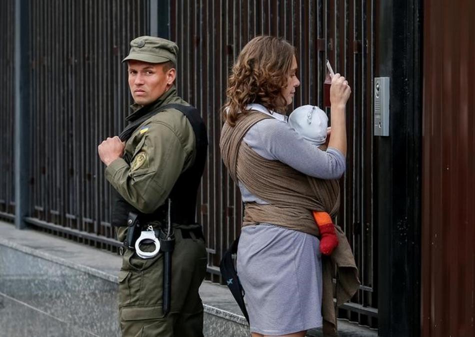 Žena přichází volit na ruskou ambasádu v Kyjevě
