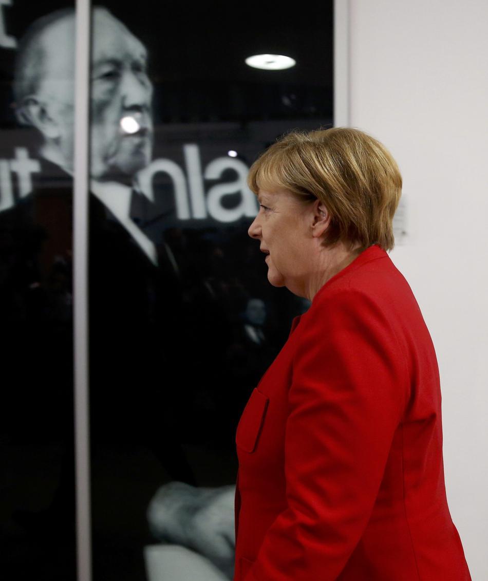 Merkelová prochází kolem fotografie Konrada Adenauera